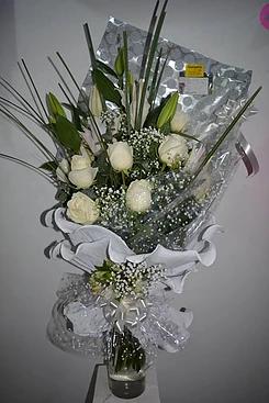 realizado con rosas blancas y lilium, detalle de flores en el moño