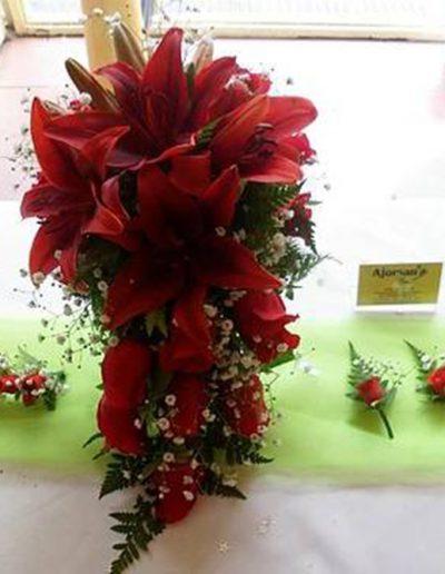 realizado con rosas y lilium rojos, tocado y boutonier haciendo juego