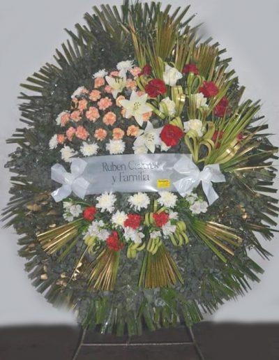 Realizada con rosas, crisantemos y liliu, detalles de follaje en motivo